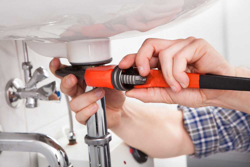 plumber fixing sink, clogged drain